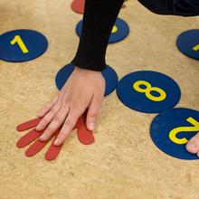 Auf dem Fußboden befinden sich runde Karten aus Karton mit Zahlen darauf sowie eine Karte in Form einer Hand. Eine Person beugt sich, um ihre Hand auf die Handkarte zu legen.