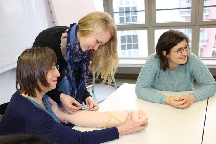 Drei Frauen sitzen am Tisch. Eine Frau übt das Spritzen an einem Therapie-Arm