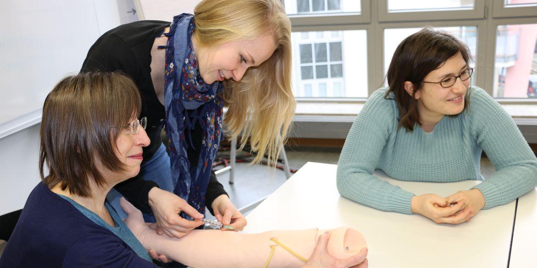 Eine Studierende des Bachelor of Science oder primärqualifizierenden Studiengangs Pflege übt das richtige Ansetzen einer Spritze an einem Atrappenarm