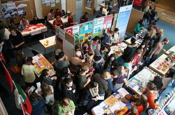 Ein stark besuchtes Audimax am International Day- Blick von oben auf die Stände der verschiedenen Partnerhochschulen der ASH Berlin.