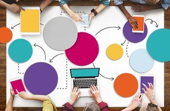 Blick von oben auf einen Tisch, auf dem bunte Kreise liegen, die mit Pfeilen verbunden sind. An dem Tisch sitzen sechs Menschen unterschiedlicher Hautfarbe mit Tablets und Laptops und scheinen zu arbeiten.