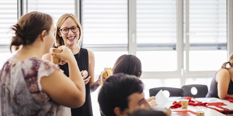 Gespräch zwischen zwei Kommilitoninnen, Studentin lacht in die Kamera