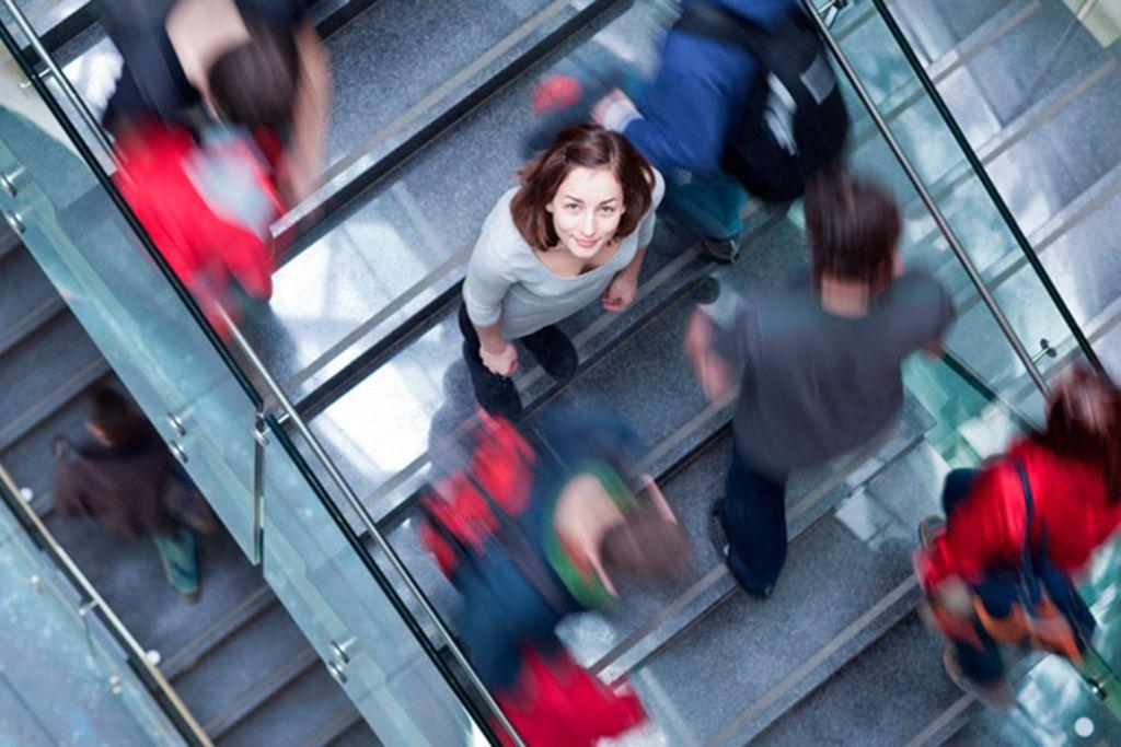 Vergrößern: Eine Frau steht auf einer Treppe und schaut nach oben in die Kamera