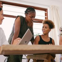 vier junge Menschen unterschiedlicher Hautfarbe diskutieren an einem Tisch