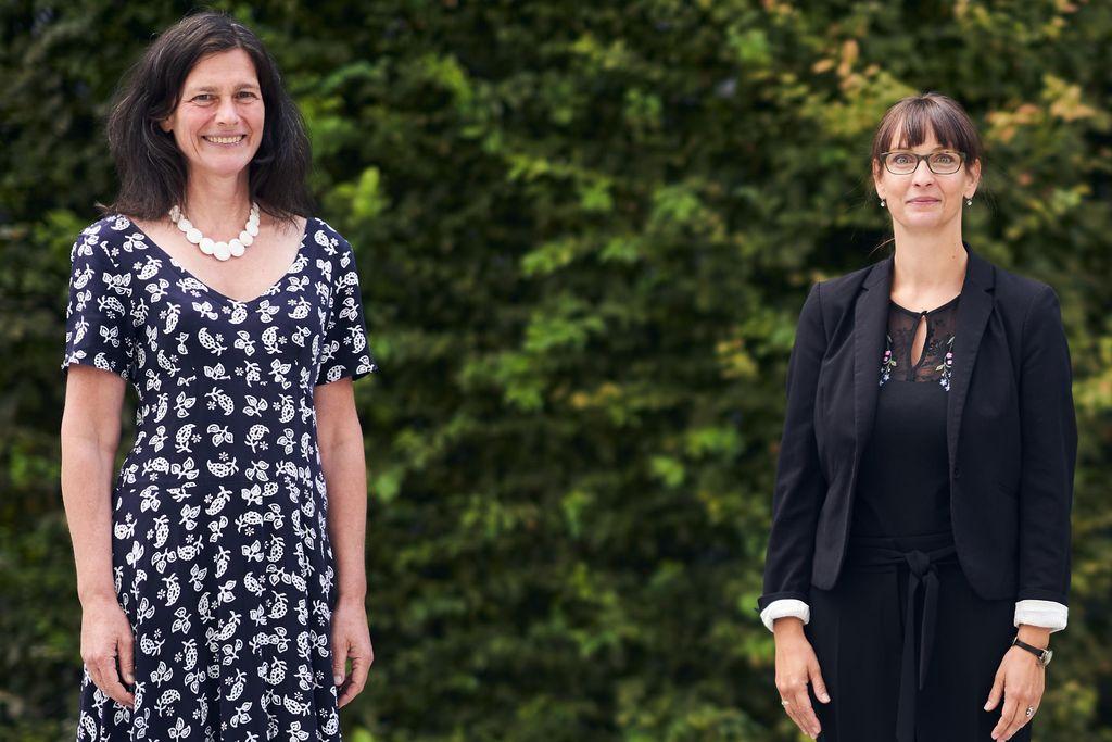 Vergrößern: Bettina Völter und Jana Einsporn stehen vor einer grünen Hecke und schauen in die Kamera