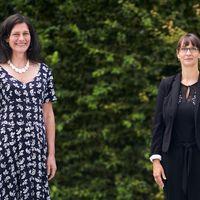 Bettina Völter und Jana Einsporn stehen vor einer grünen Hecke und schauen in die Kamera