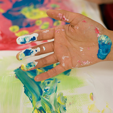 Eine Hand ist voll mit verschiedenen Fingermalfarben, mit denen ein Papier bunt bemalt wurde.