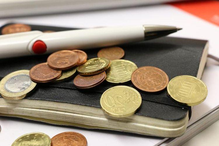 Nahansicht eines Notizbuches, auf dem viel Kleingeld und ein Stift liegt.
