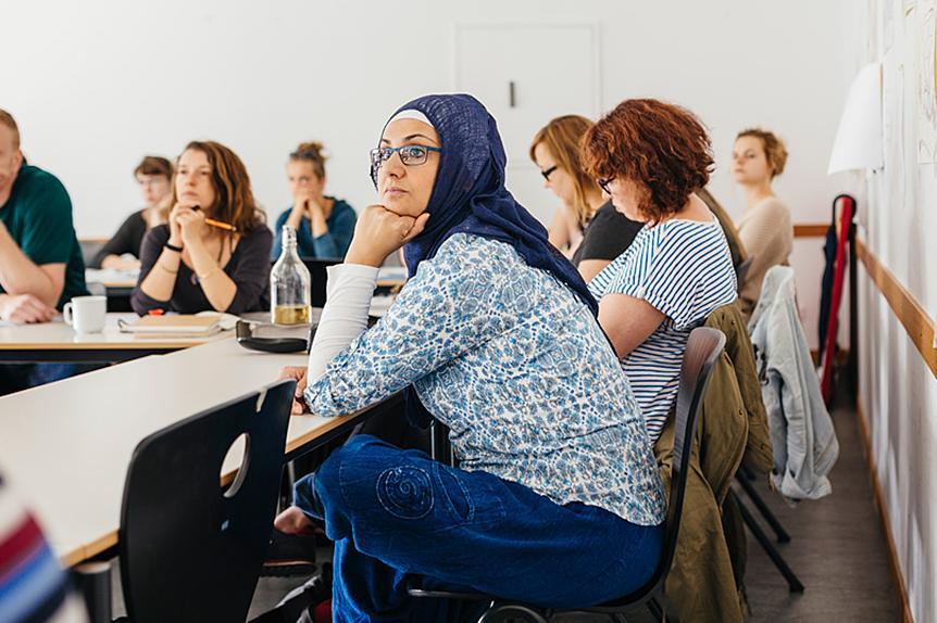 Studierende sitzen am Tisch in einem Seminarraum der ASH Berlin. Sie haben ihre Hände auf dem Tisch abgestützt und hören aufmerksam zu.