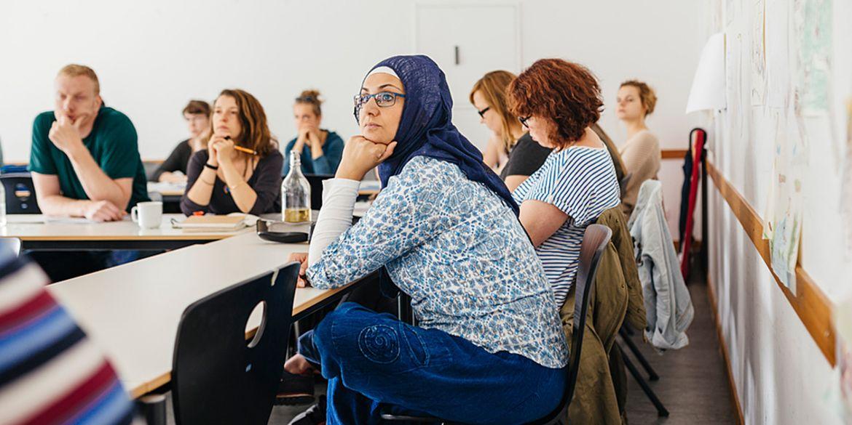 Studierende des Pre-Studies for Refugees Studiengangs sitzen am Tisch in einem Seminarraum der ASH Berlin Sie haben ihre Hände auf dem Tisch abgestützt und hören aufmerksam zu
