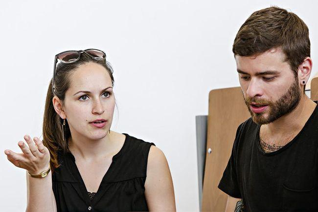 Eine Studentin diskutiert gestikulierend, ein Student hört zu.