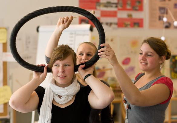 Eine Frau testet gespannt ein außergewöhnliches Hörrohr, wobei ein Ende am einen Ohr und das andere Ende des Rohres am anderen Ohr anliegt. Zwei Personen helfen der Frau beim Ausprobieren des Gerätes und machen Geräusche, indem sie auf das Rohr klopfen.