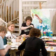 Eine Gruppe Studierende sitzt am großen Arbeitstisch der Werkstatt und malt an Bildern.