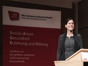 Rektorin Prof. Dr. Bettina Völter bei der Neujahrsbegrüßung an einem Pult, im Hintergrund eine ASH Stellwand