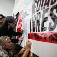 Ein Plakat vor dem Menschen stehen und Andrea Plöger mit Mütze unterzeichnet darauf