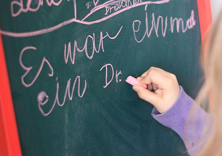 """Kinderhand, die auf Tafel """"Es war einmal ein Dr."""" schreibt"""