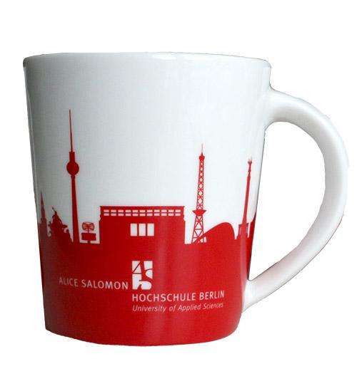 Auf der wohlgeformten rot-weiß gehaltenen Porzellantasse ist eine Berliner Skyline abgebildet. Das Hochschulgebäude darf in der Skyline nicht fehlen.
