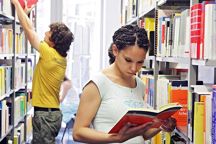 Zwei Studierende stehen vor einem Regal, er greift gerade nach einem Buch, sie hat eines geöffnet und liest darin.
