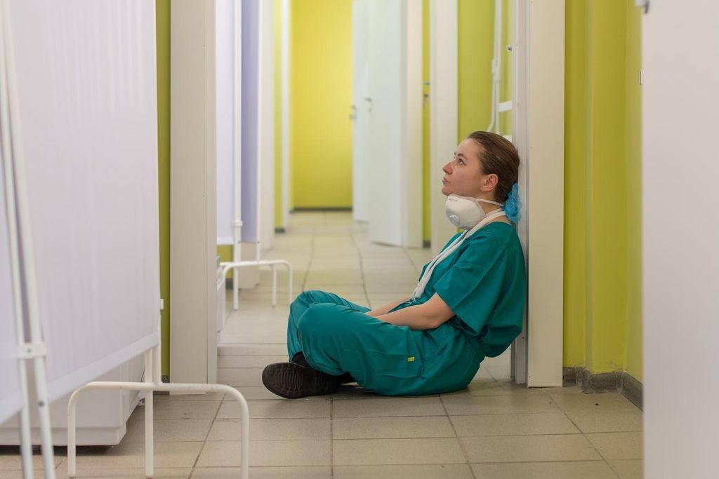 Vergrößern: Erschöpfte Pflegende sitzend auf dem Krankenhausflur