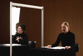 Die zwei Sprecherinnen am Tisch, zwischen ihnen eine durchsichtige Stellwand