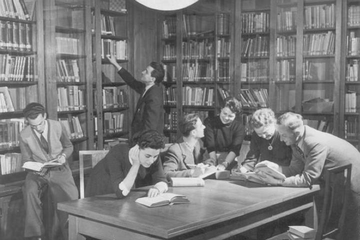 Historische schwarz-weiß-Aufnahme von Wissenschaftlerinnen und Wissenschaftlern, die sich in einer mit vielen Büchern gefüllten Bibliothek befinden und miteinander diskutieren.