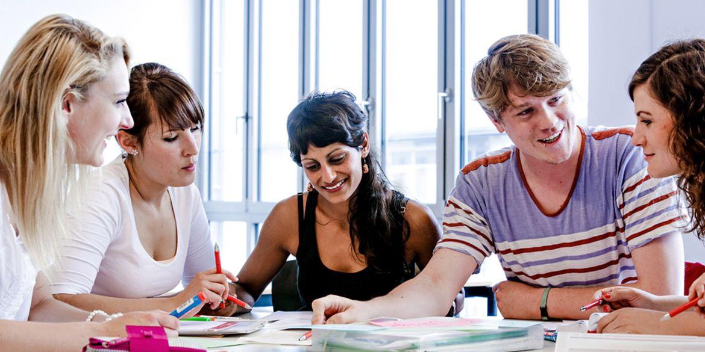 Fünf Studierende sitzen an einem Tisch, aufgeschlagene Bücher vor sich, und unterhalten sich angeregt.