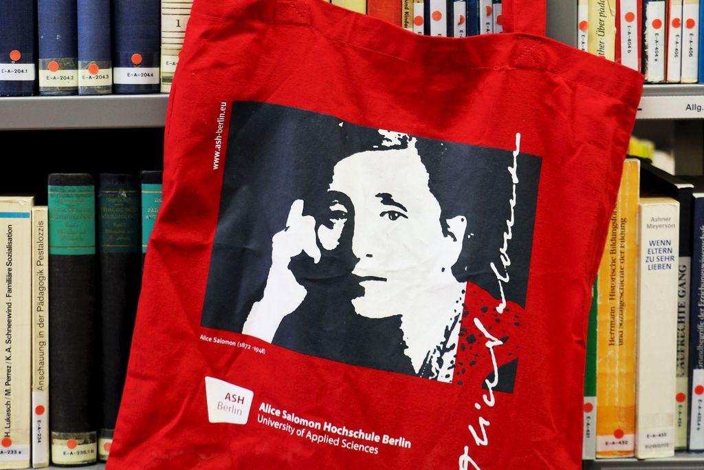 Vergrößern: Beutel mit ASH Logo und Bild von Alice Salomon hängt an Bücherregal
