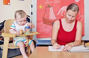 Eine Mutter arbeitet am Schreibtisch, daneben sitzt ihr Kind im Kinderstuhl und spielt mit seinem Fläschchen