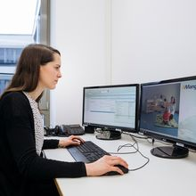 Eine Frau guckt sich auf einem Bildschirm, die aufgenommene Videografie an und wertet diese aus.