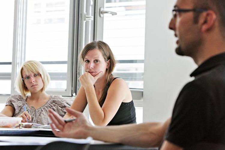 Unterrichtssituation: Dozent sitzt vor 2 Studierenden und erklärt etwas.