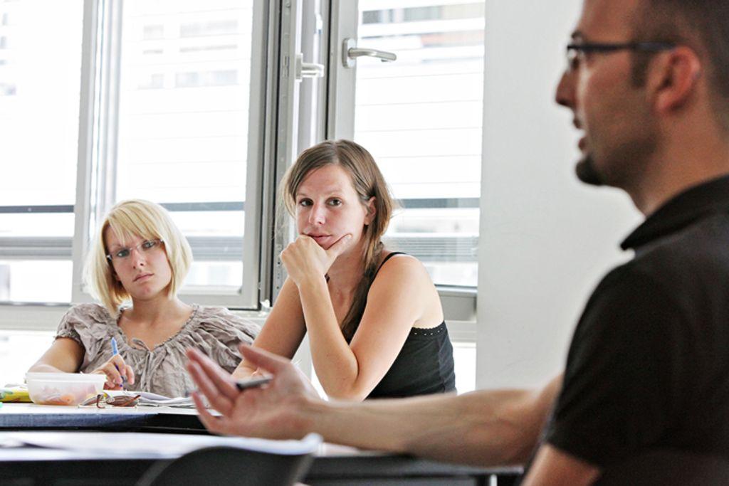 Vergrößern: Unterrichtssituation: Dozent sitzt vor 2 Studierenden und erklärt etwas.