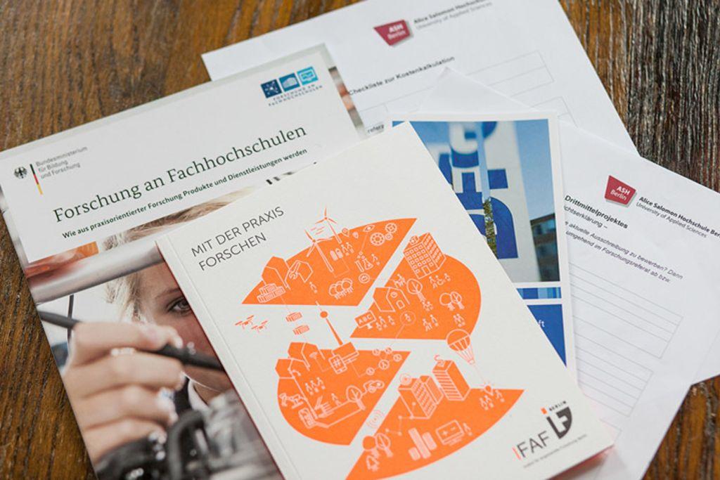 """Vergrößern: Blick von oben auf verschiedene Broschüren von Drittmittelgebern, darunter das IFAF Berlin, lesbar sind die Titel """"Forschung an Fachhochschulen"""" und """"Mit der Praxis forschen"""""""