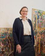 Dagmar Bergs-Winkels steht vor zwei Gemälden, die an einer weißen Wand angelehnt sind