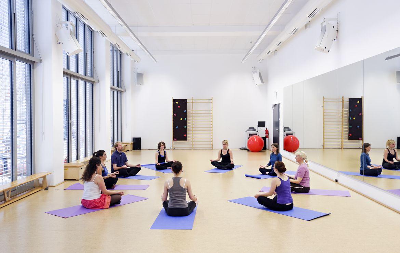 Menschen sitzen auf Sportmatten im Kreis und machen Yogaübungen