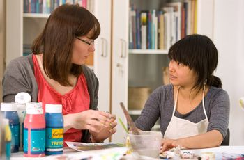 Zwei Studentinnen arbeiten in der Werkstatt und diskutieren über ihre Bilder.