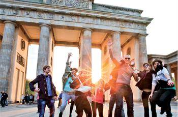 Vor dem Berliner Panorama des Brandenburger Tors springt eine Gruppe Studierender in die Luft.