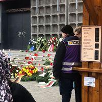 Ein Mann mit einer Weste von PSNVNET steht vor der Treppe der Gedächtniskirche mit Kerzen auf dem Boden