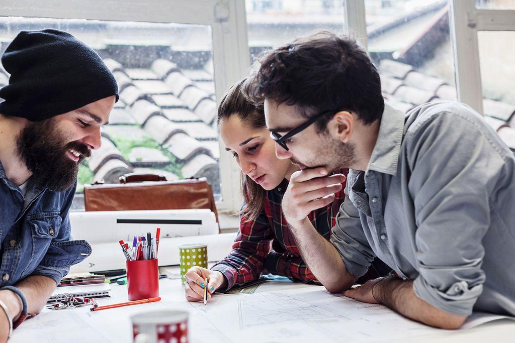 Vergrößern: Drei Studierende sitzen gebeugt über einem gemeinsamen Projekt.