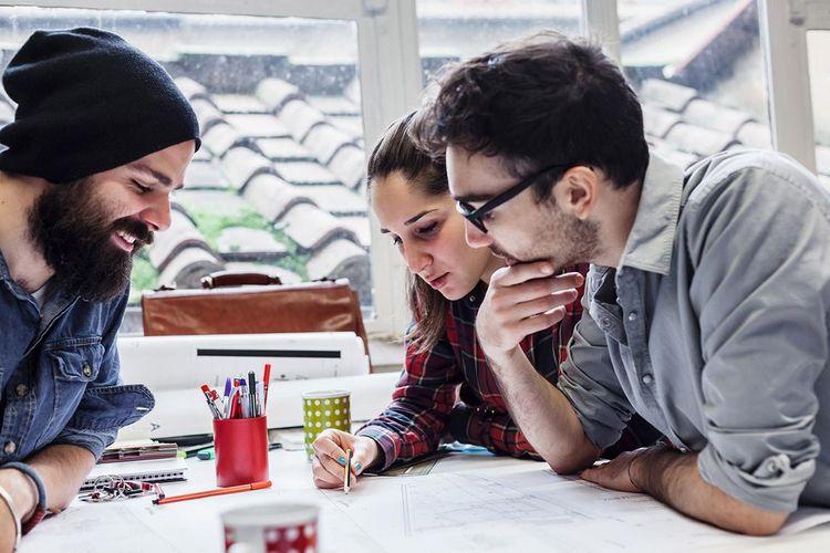 Drei Studierende sitzen gebeugt über einem gemeinsamen Projekt.