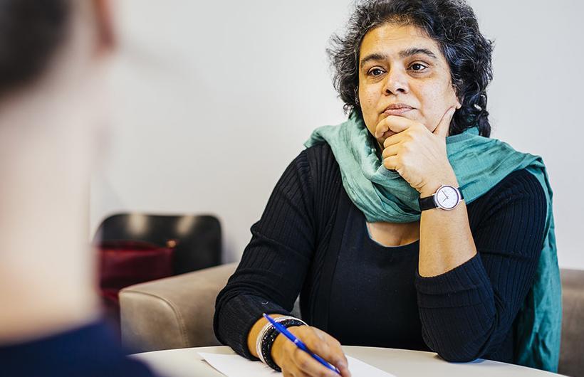 Interview-Situation: Eine Probantin ist nur von hinten sichtbar und scheint zu erzählen, eine Professorin hört aufmerksam zu.